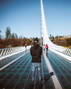 Man standing on Sundial Bridge in Redding with Vibe Dispensary Hat
